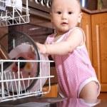 Baby at dishwasher in kitchen — Stock Photo