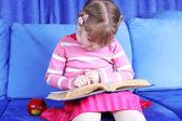 Flickan läsa bok med apple på soffa — Stockfoto