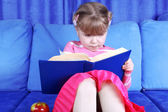 Girl reading book with apple at sofa — Stockfoto