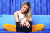 Woman working with PC at home in sofa — Stock Photo
