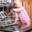Baby at dishwasher in kitchen — Stock Photo