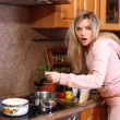 Funny surprised woman cooking dinner in the kitchen — Stok fotoğraf