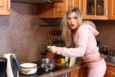 Funny surprised woman cooking dinner in the kitchen — Stock Photo