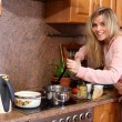 Funny woman cooking dinner in the kitchen — Stock Photo