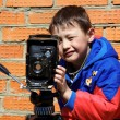 Kid making a shot with retro camera on tripod — Stock Photo