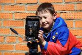 Kid making a shot with retro camera on tripod — Stock Photo