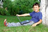 Jongen met laptop zitten op boom buitenshuis — Stockfoto