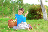 Little boy posing outdoors with apples — Stock Photo