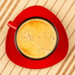 Red coffee cup on striped tablecloth — Stockfoto