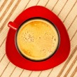 Red coffee cup on striped tablecloth — Stock Photo #2820668