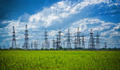 Summer meadow with high-voltage towers — Stock Photo