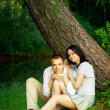 Young couple sitting under tree — Stock Photo #3654921