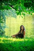 Woman sitting on riverside — Stock Photo