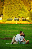Young couple sitting on park lawn — Stock Photo
