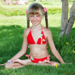 Little girl sit in lotus position and meditate. - Stock Photo