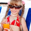Child in sunglasses and red bikini drink juice. — Stock Photo
