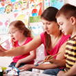 Child with teacher draw paints in play room. — Stock Photo #3317715