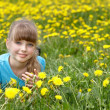 Little girl lying on grass in flower. - Stock Photo