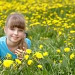 Little girl lying on grass in flower. — Stock Photo