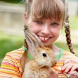 Stock Photo: Happy girl feed rabbit with carrot.