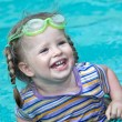Happy little girl looking out from swimming pool — Stock Photo