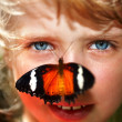 Happy child with butterfly on neck. - Stock Photo