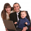 Happy family with laptop and headset. — Photo