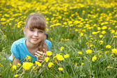 Little girl lying on grass in flower. — Stock Photo
