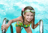 Girl in goggles leaves pool. — Stockfoto