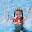 Girl with red swimsuit splashing in swimming pool. — Stock Photo