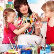 Children painting with teacher in preschool. — Stock Photo