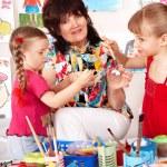 Children painting with teacher in preschool. — Stock Photo #3321151