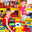 Foto Stock: Child with puzzle, block and construction set in play room.