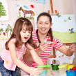 Child painting  with teacher in preschool. - Foto de Stock