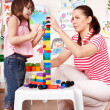 Child with wood block and construction set in play room. — Stock Photo #3321196