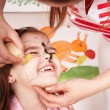 Child with paint of face in play room. — Stockfoto