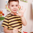 Child with brush draw red sun in play room. - Stock Photo