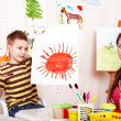 Child with teacher draw paint in play room. — Stok fotoğraf