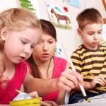 Children painting with teacher. — Stock Photo