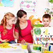 Child with teacher draw paints in play room. — Stock fotografie