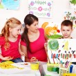Child with teacher draw paints in play room. — Stok fotoğraf
