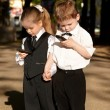Children in business suit with mobile phone outdoors. — Stock Photo