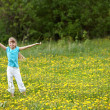 Child on meadow  with hand up. — Stock Photo