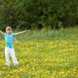 Photo: Child on meadow with hand up.
