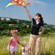 Happy family and children fly kite. — Stock Photo