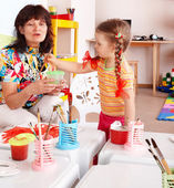 Child with teacher draw paints in playroom. — Stock Photo