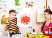 Child with teacher draw paint in play room. — Stock Photo