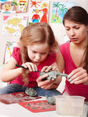 Child girl mould from clay in play room. — Stock Photo