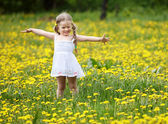 Little girl on grass in flower. — Stock Photo