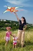 Crianças e família feliz empinar pipa. — Foto Stock